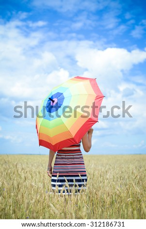 Elegant female holding umbrella and standing in golden wheat field. Backview of woman in striped dress who looking into the distance over blue sky background - stock photo