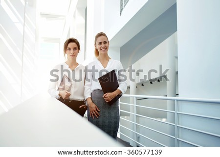 Elegant female lawyers holding touch pad and folder while standing in office interior after successful meeting, women professional employers in good mood resting after presentation with digital tablet - stock photo