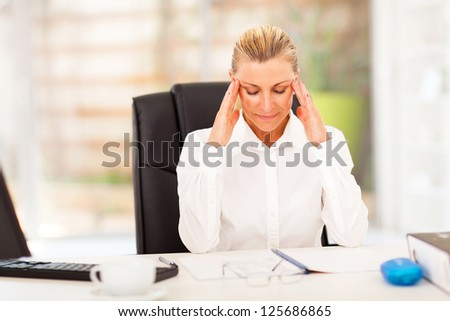 elegant female middle aged office worker resting in office - stock photo