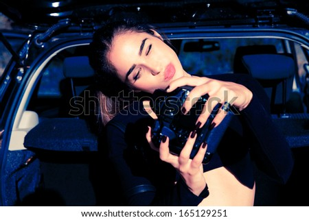 Elegant female photographer holding a digital camera. Outdoors horizontal shot . Attractive woman by a car. Fanny girl. - stock photo