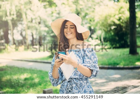 Elegant female with a hat on her head in park. Young woman with long hair,  smiling and make selfie on her mobile phone.