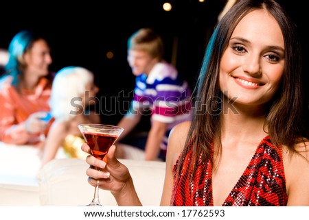 Elegant female with glass of martini rossa looking at camera on background of her friends