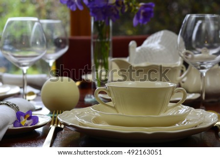Elegant festive dinner party table in front of garden window background.