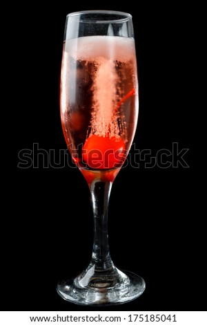 Elegant flute of effervescent pink champagne with bubbles flowing from a maraschino cherry for a romantic date over a black background - stock photo