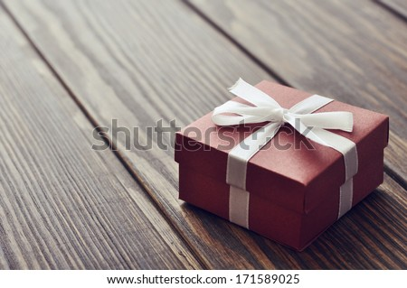 Elegant gift box on a wooden background closeup - stock photo