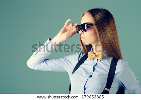 Elegant girl model poses in blouse, bow tie and black sunglases. Fashion shot. - stock photo