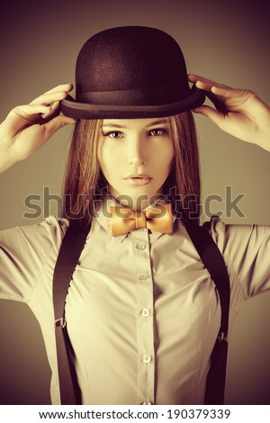 Elegant girl model poses in blouse, bow tie and bowler hat. Refined style of old Europe. - stock photo