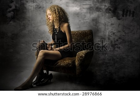 elegant girl sitting on armchair - stock photo