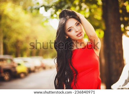 Elegant girl with beautiful makeup and hair in a red dress - stock photo