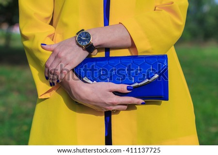 Elegant girl with blue handbag clutch in hand . Stylish outfit with accessories watch - stock photo