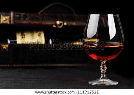elegant  glass of cognac and bottle in wooden case  background - stock photo