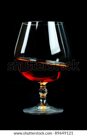 elegant  glass of cognac on table. black background - stock photo