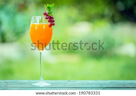 Elegant glass of fresh orange juice or orange and champagne blend garnished with a bunch of ripe red currants standing on a picnic table in the garden on a summer day - stock photo