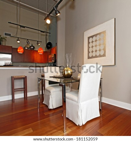Elegant glass table with white luxury chairs in modern reconstructed living room. Decorated with vase and plates. View of the kitchen