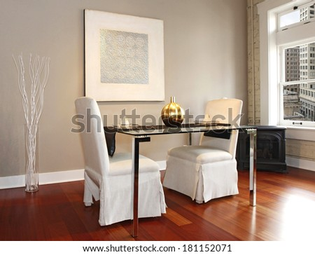 Elegant glass table with white luxury chairs in modern reconstructed living room. Decorated with glass vase and white dry branches and wall picture - stock photo