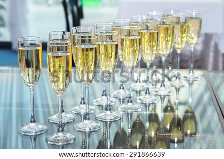 Elegant glasses with champagne standing in a row on serving table during party or celebration - stock photo