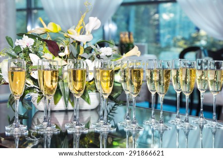 Elegant glasses with champagne standing in a row on table during party - stock photo