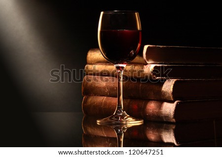 Elegant goblet of red dry wine near old books on dark background - stock photo