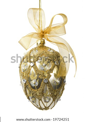 Elegant gold and silver bejeweled egg-shaped ornament with gold mesh bow (includes clipping path). - stock photo
