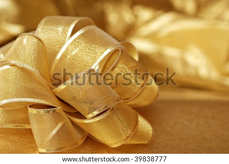 Elegant gold gift bow with shiny wrapping paper in background.  Macro with extremely shallow dof. - stock photo