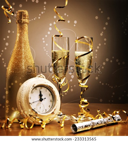 Elegant gold New Year still life with a clock counting down to midnight in front of a bottle and flutes of sparkling champagne with golden streamers and a bokeh of effervescent bubbles - stock photo