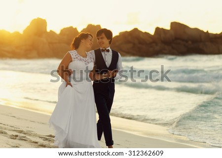 elegant gorgeous bride and groom walking in sunset on the background of  the ocean and a beach, wedding ceremony in Seychelles