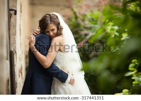 elegant gorgeous happy  brunette bride and groom standing on the background of a old building in Lviv - stock photo