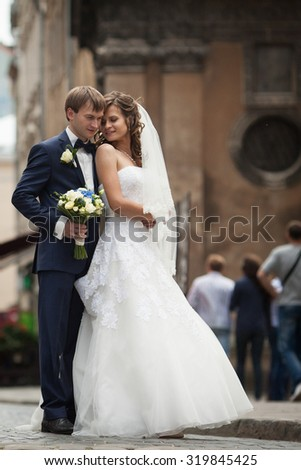 elegant gorgeous happy  brunette bride and groom standing on the background of a old building in Lviv