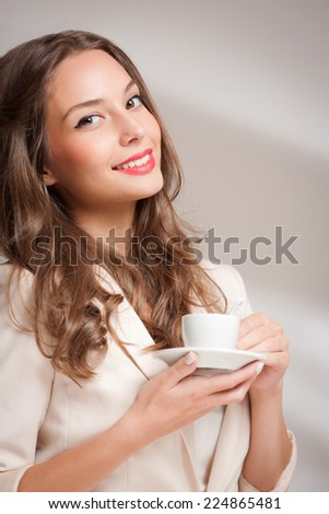 Elegant gorgeous young brunette woman with a cup of gourmet coffee.