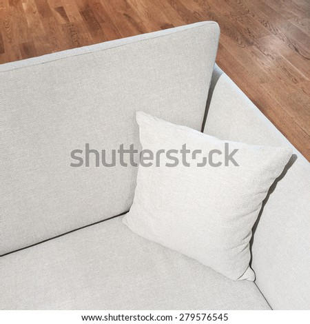 Elegant gray sofa with cushion on wooden floor. - stock photo