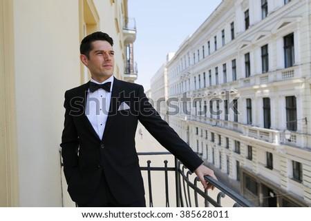 Elegant groom on balcony posing - stock photo