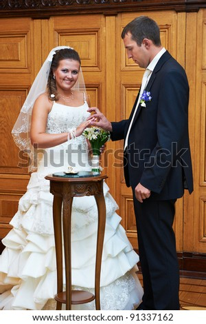 Elegant groom wears a wedding ring a happy bride. Solemn registration of marriage.