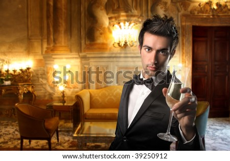 elegant guy holding a glass of wine in a luxury interior - stock photo
