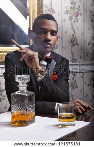 Elegant, handsome black man enjoy whiskey and cigar in the club - stock photo