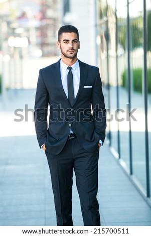 elegant handsome business man walking on the street - stock photo