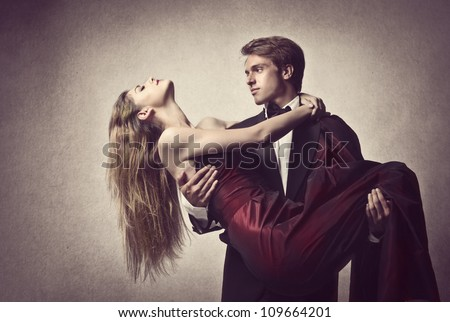 Elegant handsome man holding his girlfriend in his arms - stock photo