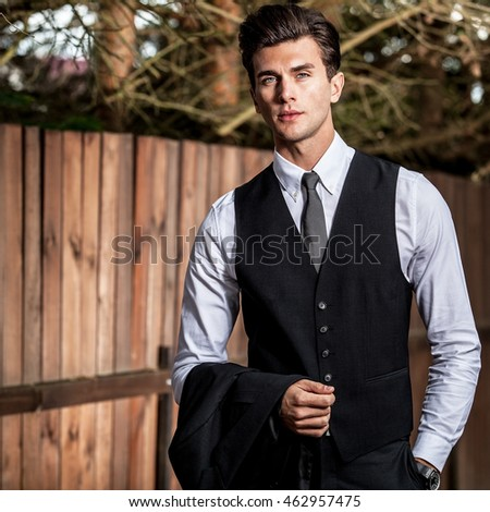 Elegant handsome man in classical suit poses near wooden fence.