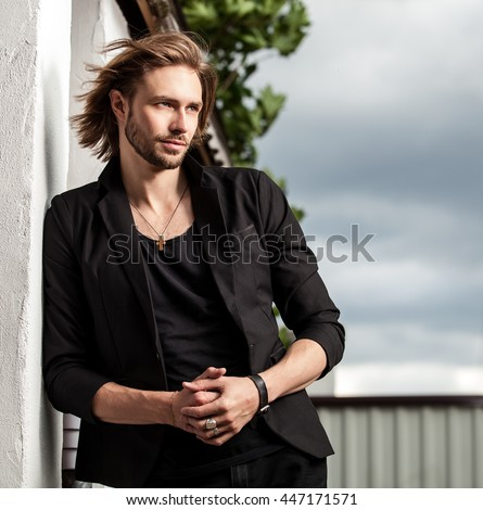 Elegant handsome man poses outdoor.  - stock photo