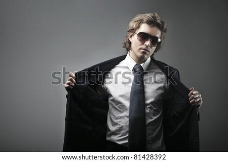 Elegant handsome man undressing - stock photo