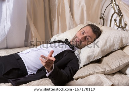 Elegant handsome playboy in a bow tie and suit reclining on a bed in an elaborate bedroom with a seductive smile on his face - stock photo