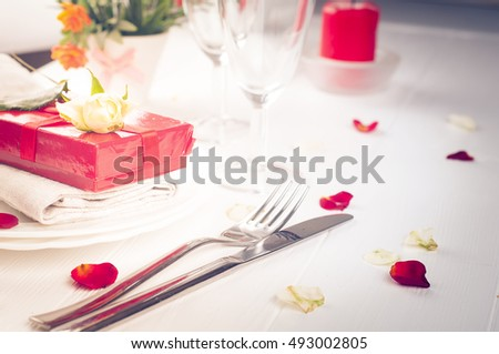 Elegant holiday table setting with red ribbon gift on white background . Toned photo