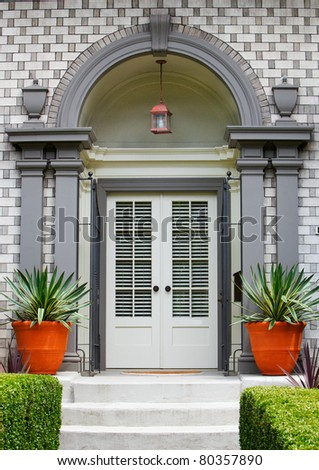 Elegant Home Front Door with gray wood arch and alternating brick work pattern - stock photo