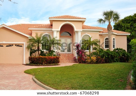 Elegant home, with huge archway covering double door entrance,  flanking columns, lush tropical landscaping and wide brick driveway joining the sidewalk  completes this modern design. - stock photo