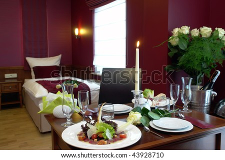Elegant hotel room with room service on a table, complete with meal, candle, wine, and flowers.