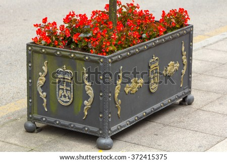 elegant iron planter with red flowers - stock photo