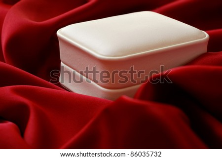 Elegant jewelry gift box nestled in red satin fabric.  Macro with extremely shallow dof. - stock photo