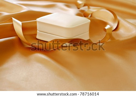 Elegant jewelry gift box on gold satin with matching ribbon. Macro with shallow dof and copy space. - stock photo