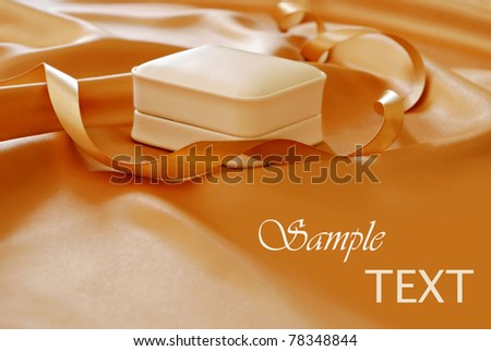 Elegant jewelry gift box on shimmery gold satin with matching ribbon.  Macro with shallow dof and copy space. - stock photo