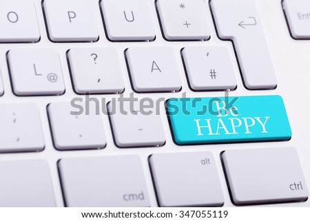 Elegant keyboard with BE HAPPY word in blue button close up photo