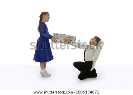 Elegant kneeling boy with angel wings gives a gift to pretty girl in blue dress isolated on white background with floor